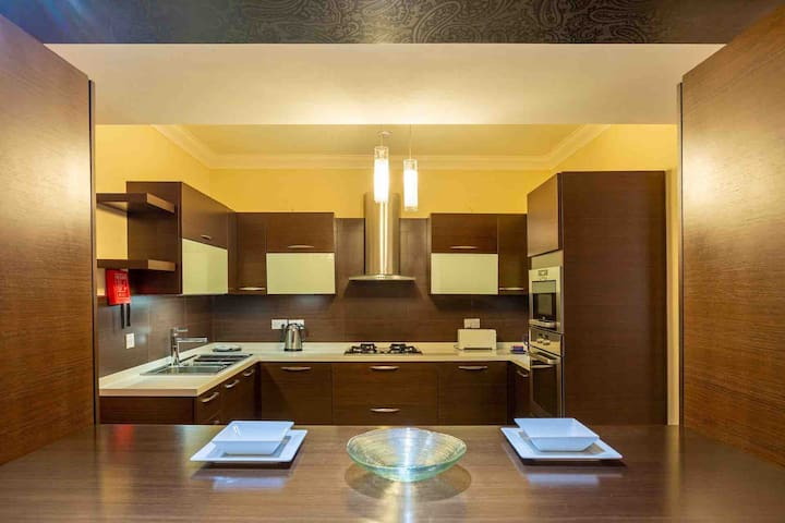 Fully functional designed kitchen by FXB which features a microwave oven, over, hob with four burners and all the amenities you will need in a kitchen should you wish to dine in.