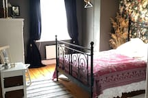 The grey room with a flowery wallpaper and an old pink lamp.