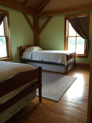 Twin bedroom has vaulted wood ceilings, a twin trundle under one bed and spare mattress under the other.