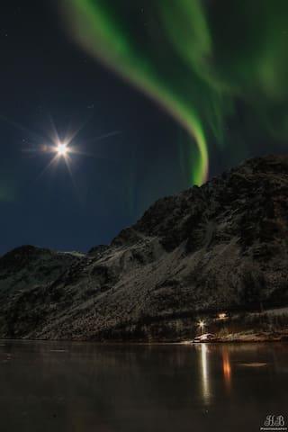 Desember kveld. Vannet nedfor hytta er islagt, nordlyset og månen speiler seg i isen.