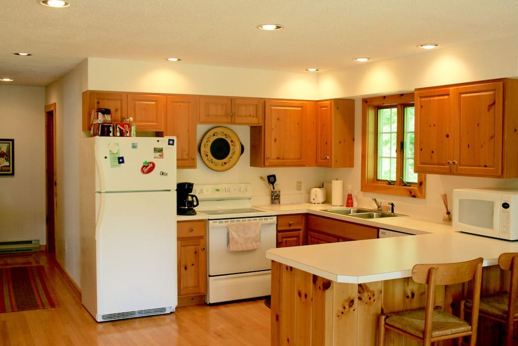Large, bright kitchen with breakfast bar, fully stocked with flatware, silverware and cookware