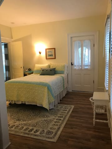Middle bedroom on main floor connects to bathroom and sitting room. Door opens to semi-private screened porch.