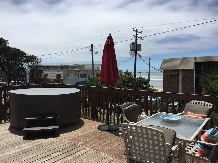 Large deck off the front of the house with hot tub and partial view of the ocean