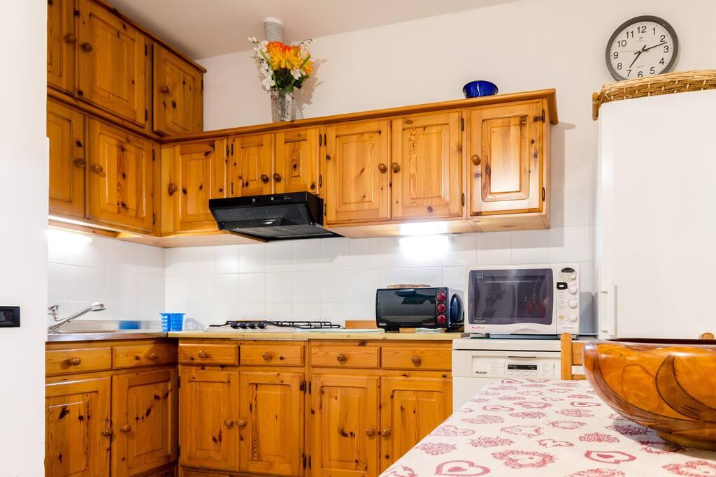 Cucina completa di angolo cottura con cappa, lavastoviglie, microonde, frigo-freezer e fornetto