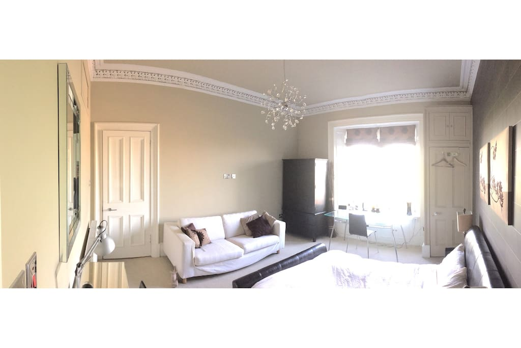Bedroom with ensuite bathroom and sofa
