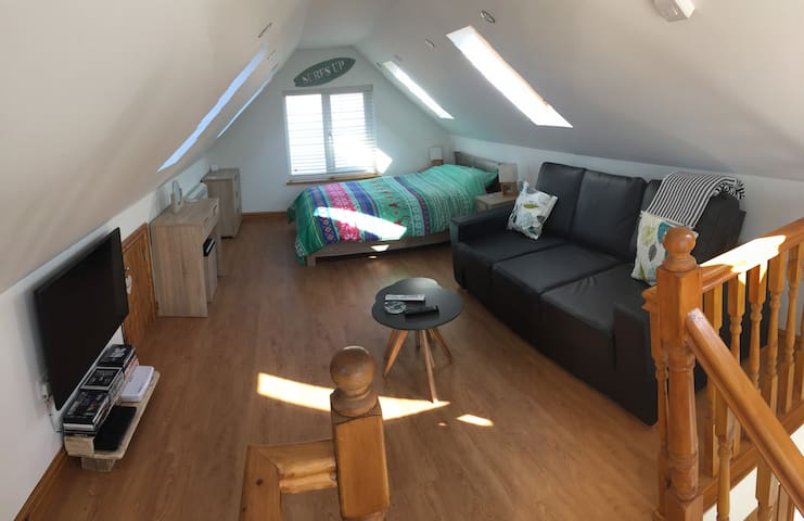 Upstairs living space with double bed and double sofa bed