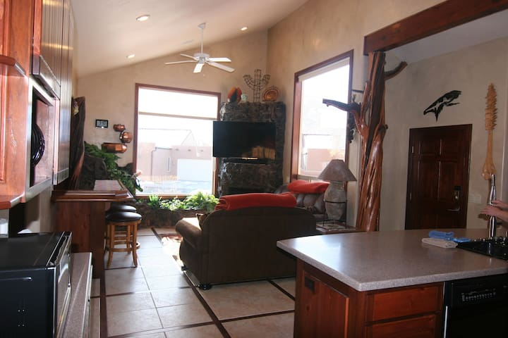 """Living room has great views of Moab Rim, 60"""" Smart HDTV, soundbar/ subwoofer sofa sleeper, loveseat wet bar area with 2 bar stools.  This area is great to use to hook up your lap too."""