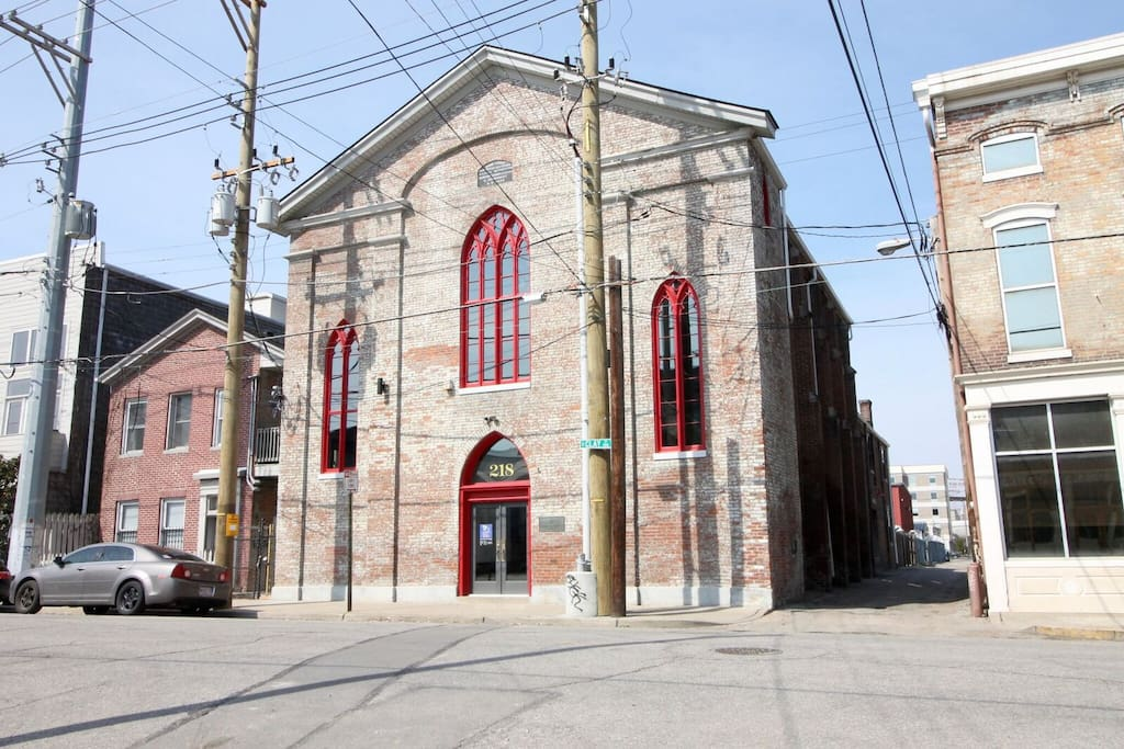 A view of the front facade of The Holy Goat. This building was designed and used as a church, until recently. It has been very well designed and repurposed as individual efficiency-style apartments.