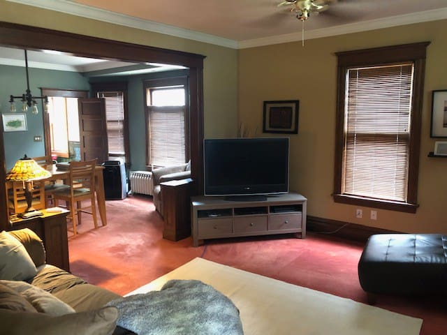 Flat screen TV, PS4, movies on dvd & complimentary wifi. Dining room table and swinging door to the kitchen in the background