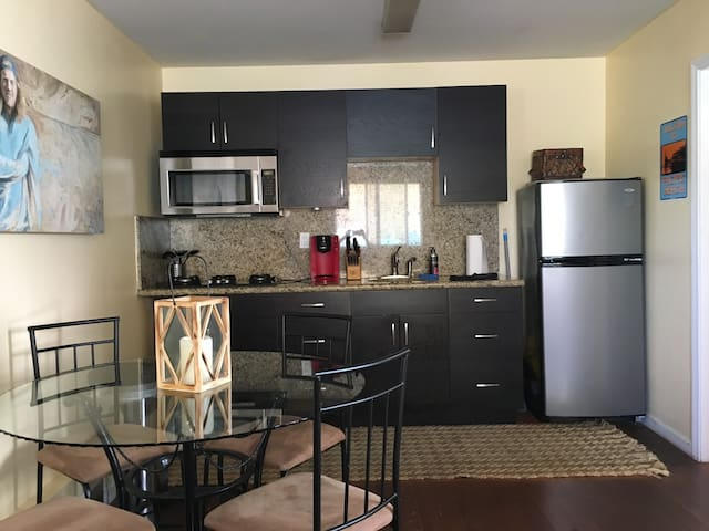 Dining table; Kitchen with amenities - Keurig, refrigerator, stove top, Brita filter, utensils, pots and pans.