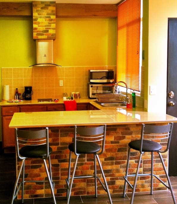 Kitchen includes bar stools, spacious counter top and contains all kitchen necessities : range hood,  ceramic cooktop stove, microwave, extra-wide toaster oven, toaster and a coffee maker.