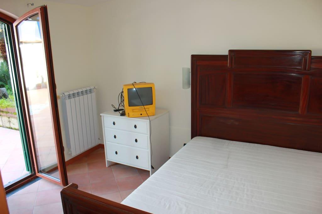 Camera da letto con letto matrimoniale, cassettiera e televisione