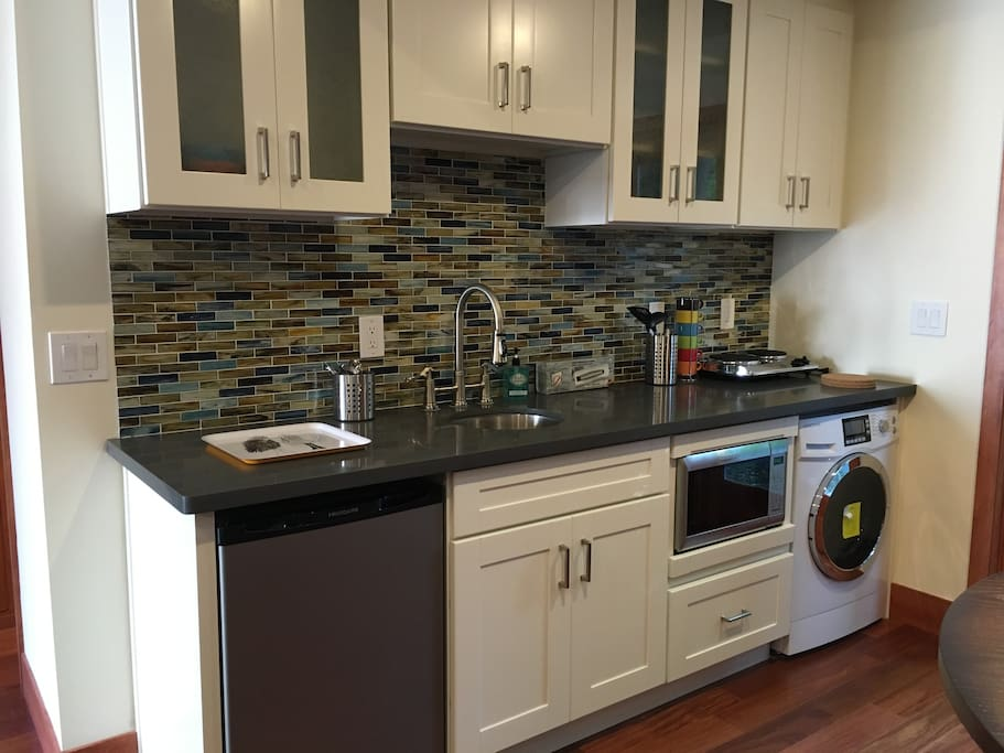 Kitchenette includes sink, small refrigerator, two burners, microwave/convection oven combo and a washer/dryer combination.
