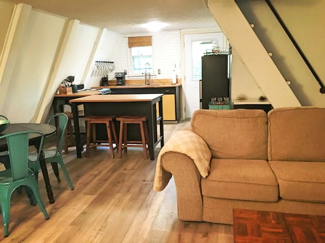 Open downstairs w/ kitchen, living, dining.  Seating for 3 at bar, 4 at dining table, and 5-6 on couch