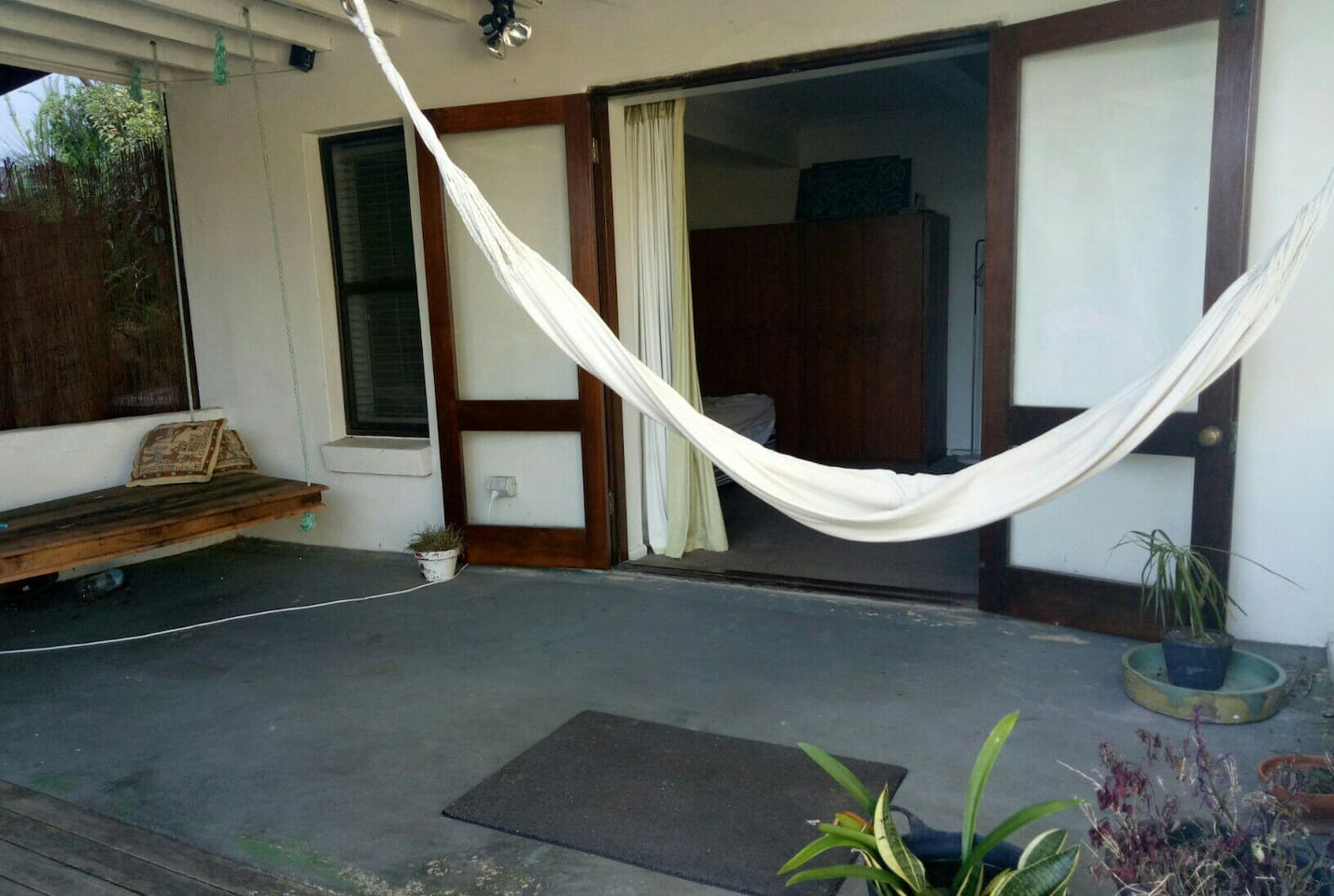 Outdoor patio area with hammock and hanging bed.