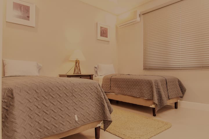 Spacious second bedroom with AC, two double beds and straw mat