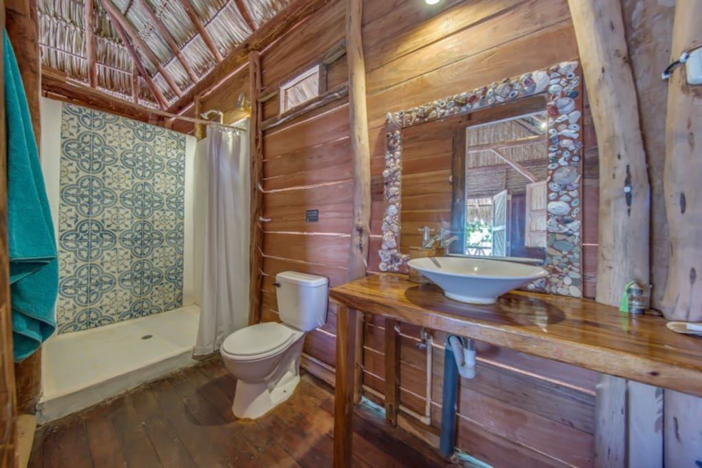 Bathroom with traditional handmade tiling, natural woods& shell mirror