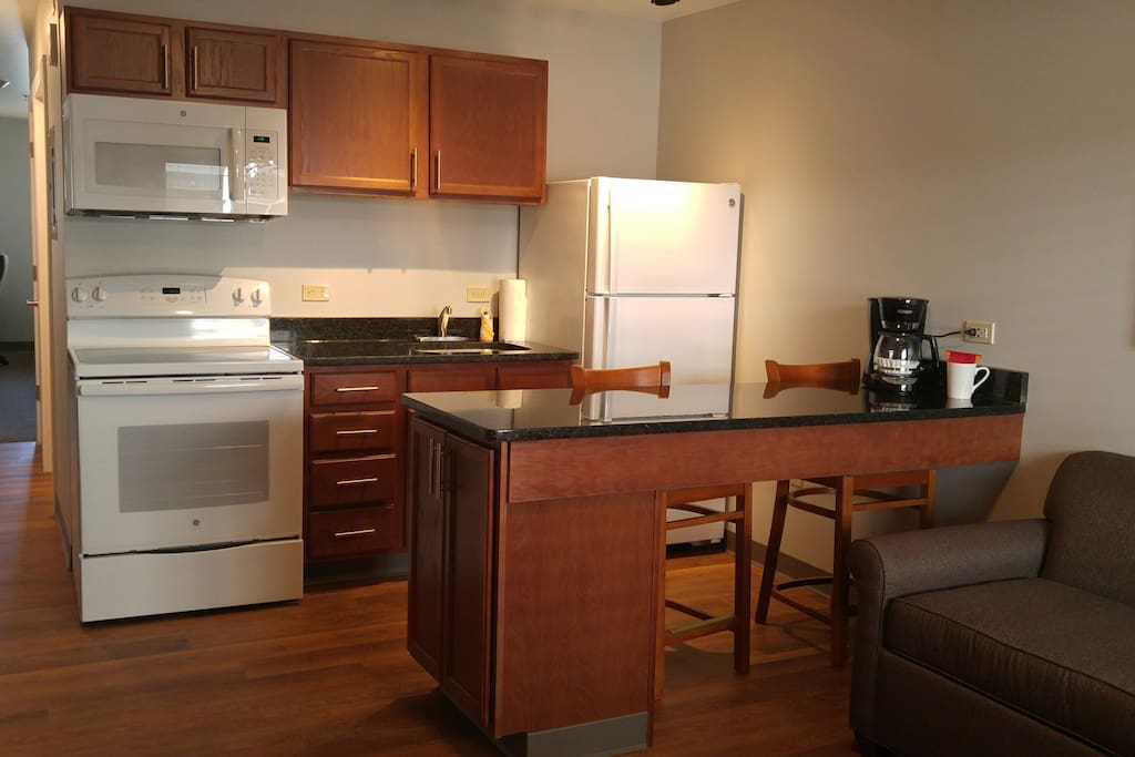 Kitchen Area includes 4 burner stove with oven, Full size refrigerator with freezer, coffee maker, microwave
