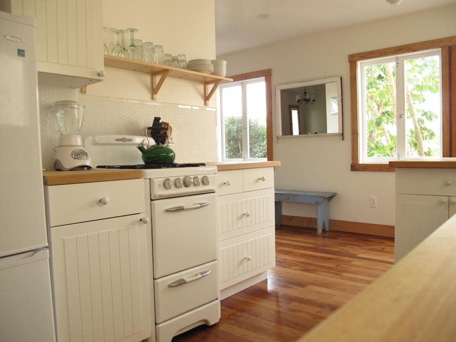 Antique stove and open farm house shelving make this a charming but easy to use kitchen.