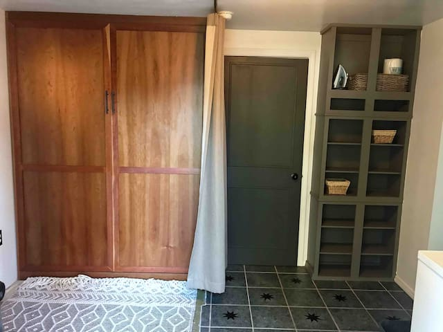 Queen Murphy bed with privacy curtain in multi-use space.  This room has an entrance and laundry room combined.