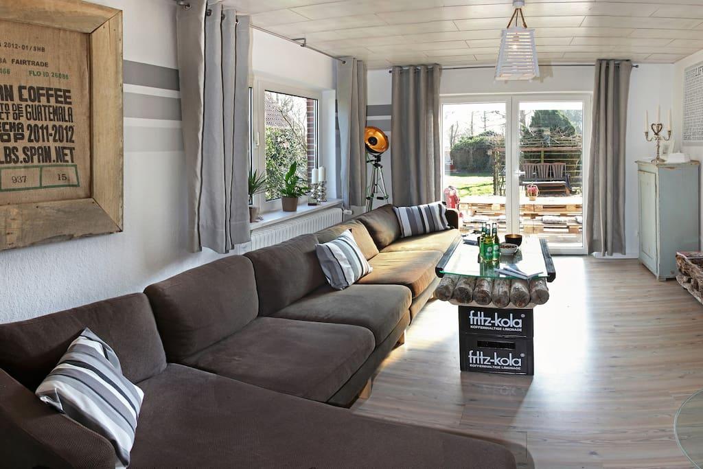 Die Wohnstube mit angeschlossener Küche hat eine große Couch, die für alle zusammen Platz bietet und einen Fernseher, sowie einem Kamin-Ofen. Durch die Tür kommt man über die Terrasse  in den Garten.
