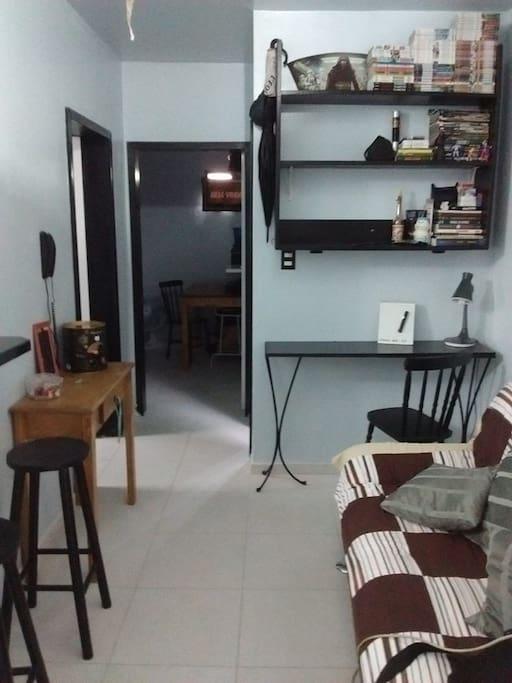 amplo quarto de casal com escrivaninha porta ao fundo do corredor.