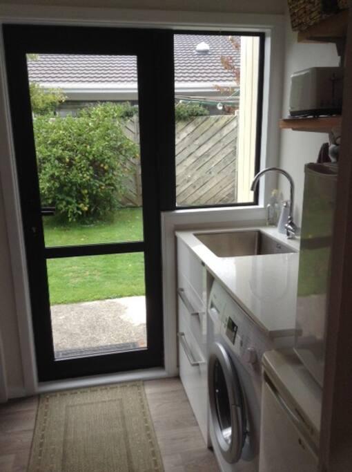 Entrance, laundry/kitchenette with sink, fridge and washing machine