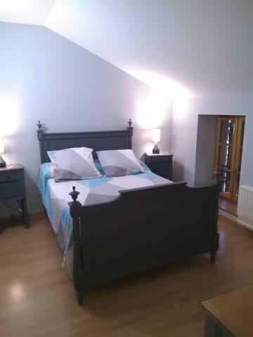 La chambre avec un lit 140*190 et son bureau, avec vue sur le jardin