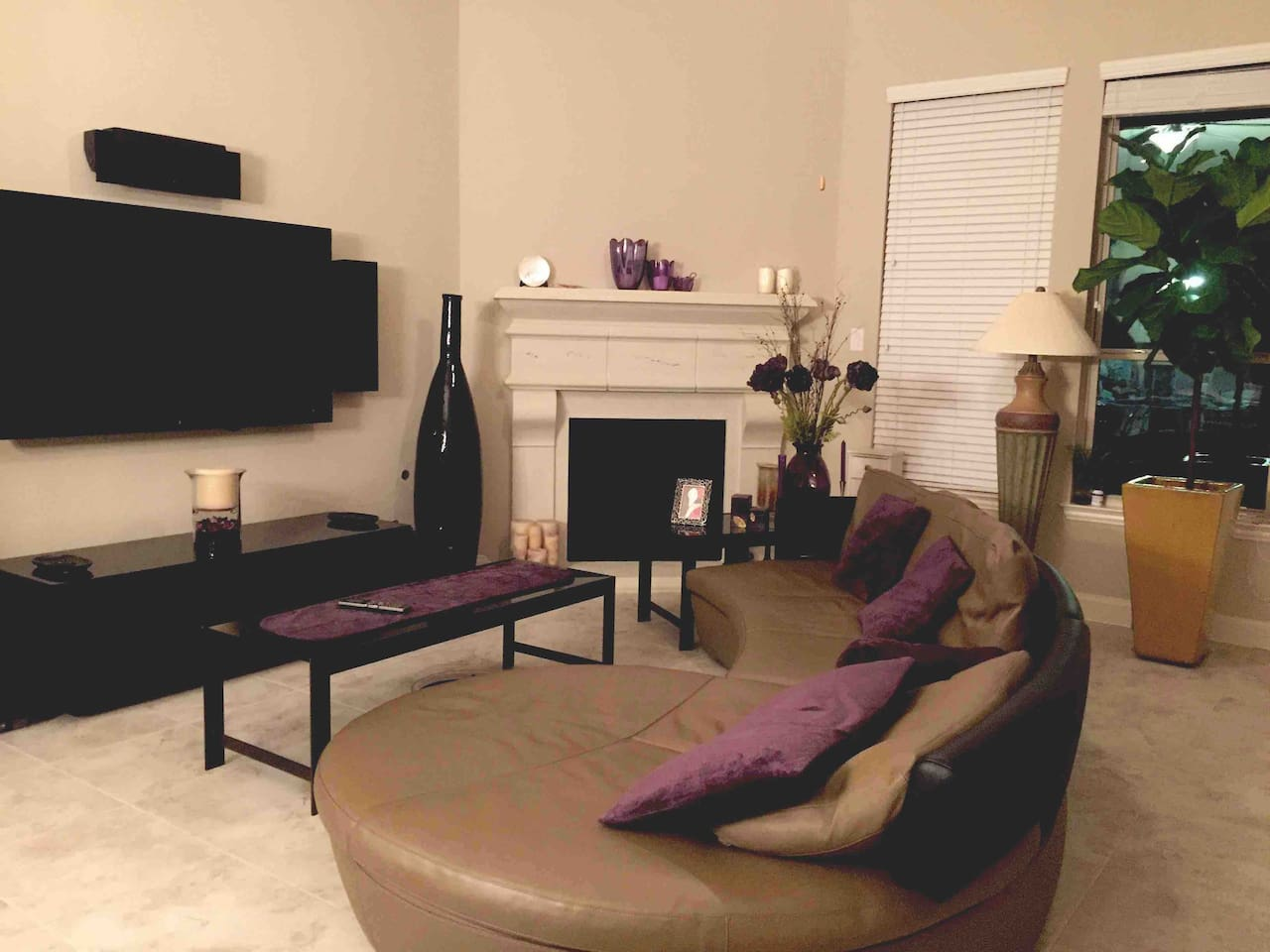 Modern home decorated in a PURPLE theme....Living room with a cozy fireplace and a very comfy leather sofa to watch TV, Netflix or HBO power by a modern Martin Logan surround sound system