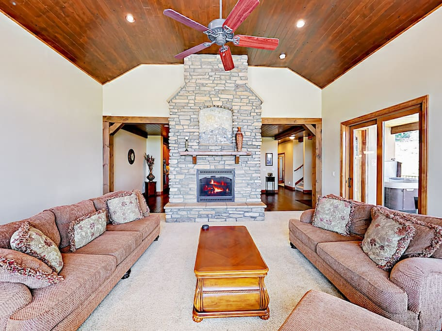 The spacious main living room features a vaulted ceiling and grand stone fireplace