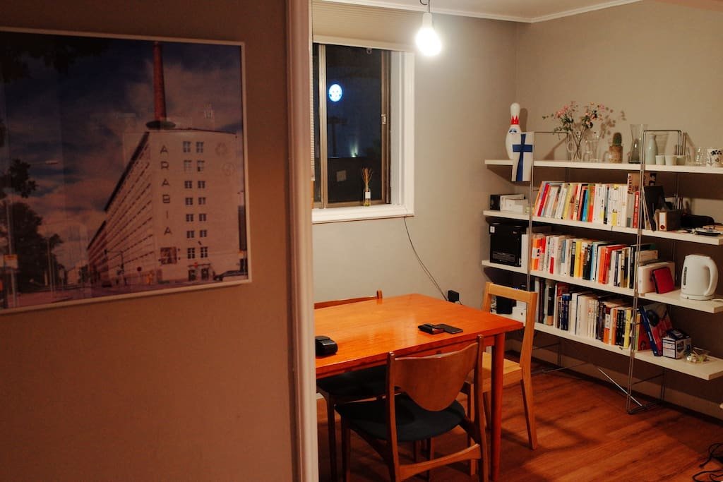 A dining room, my favourite spot in my house. A big wooden dining table, a window that offers nice view, and a bookshelf filled with my favourite books and objects.