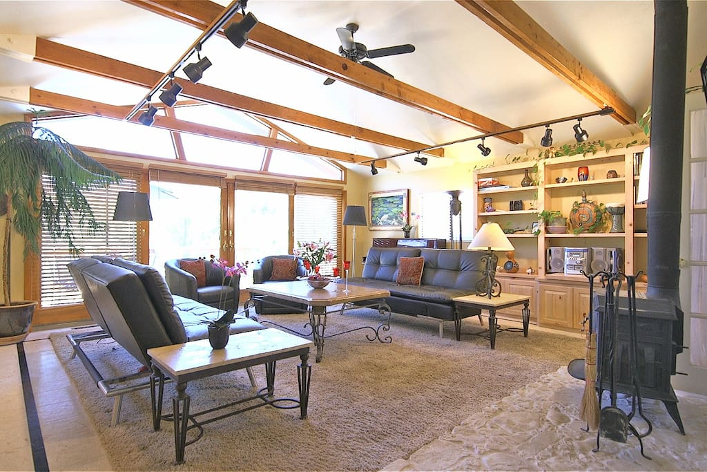 Living room features vaulted ceilings, hi def TV and a large private deck