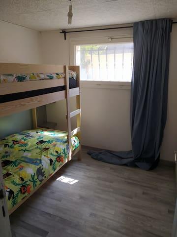 La chambre , avec lit superposé en 90x200 donc adapté pour adultes même si la décoration (linge de lit ) est axé pour des enfants .