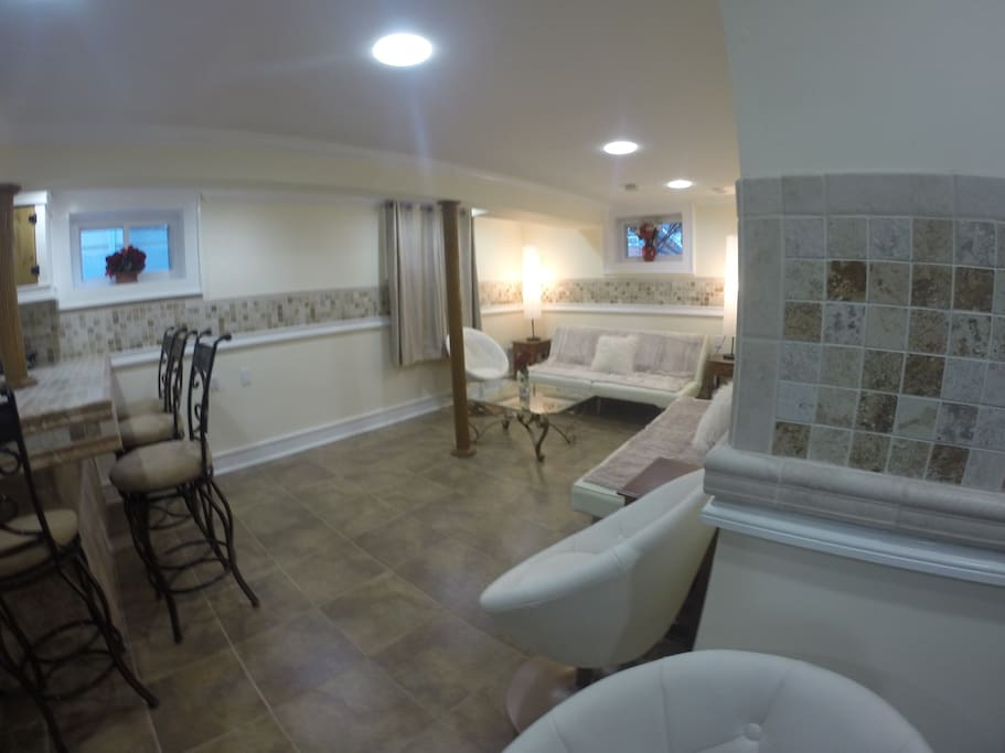 Living room and edge of kitchen from open area - - wifi, cable TV, and all utilities included!