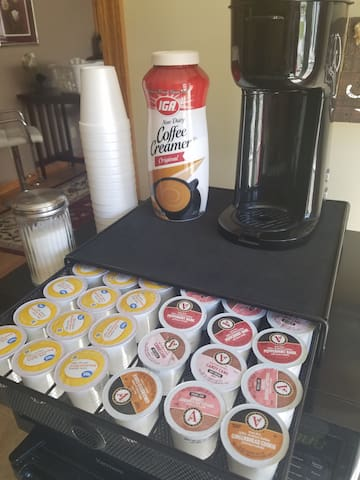 Keurig maker with variety of pods provided as well as creamer, sugar and cups.