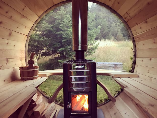 Wood-burning Barrel Sauna available for complimentary guest use, with portal view of the meadow and forest.
