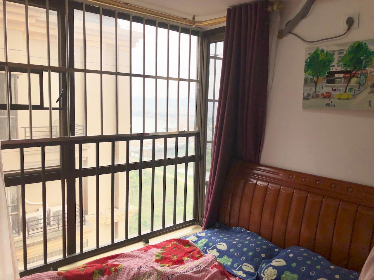 这是房客会居住的房间,窗外可以看到一些江景。床头的墙上挂着我先生画的画,画的是他家乡的一角街景。