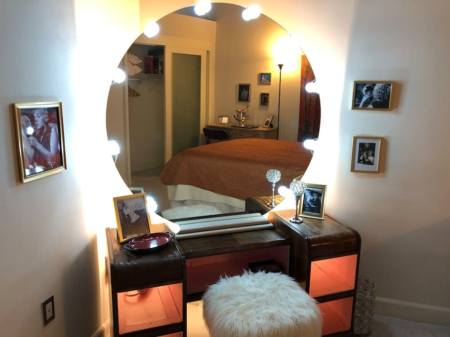 Vintage, custom-built vanity complete with backlighting and pink shelves, surrounded by pics of Marilyn getting made up!