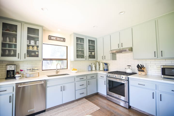 Updated, fully-stocked kitchen with granite countertops, subway tile backsplash, and stainless steel appliances.