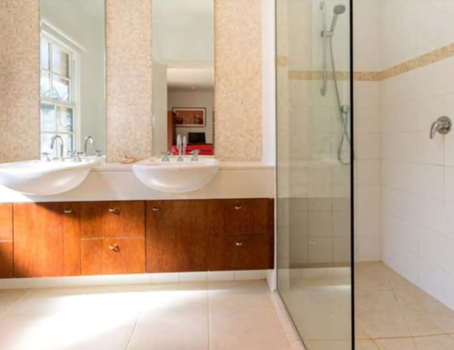 A spacious ensuite with walk in shower and double basins. Towels, shampoo, conditioner, body and hand wash are all provided. Just bring your own beach towel.