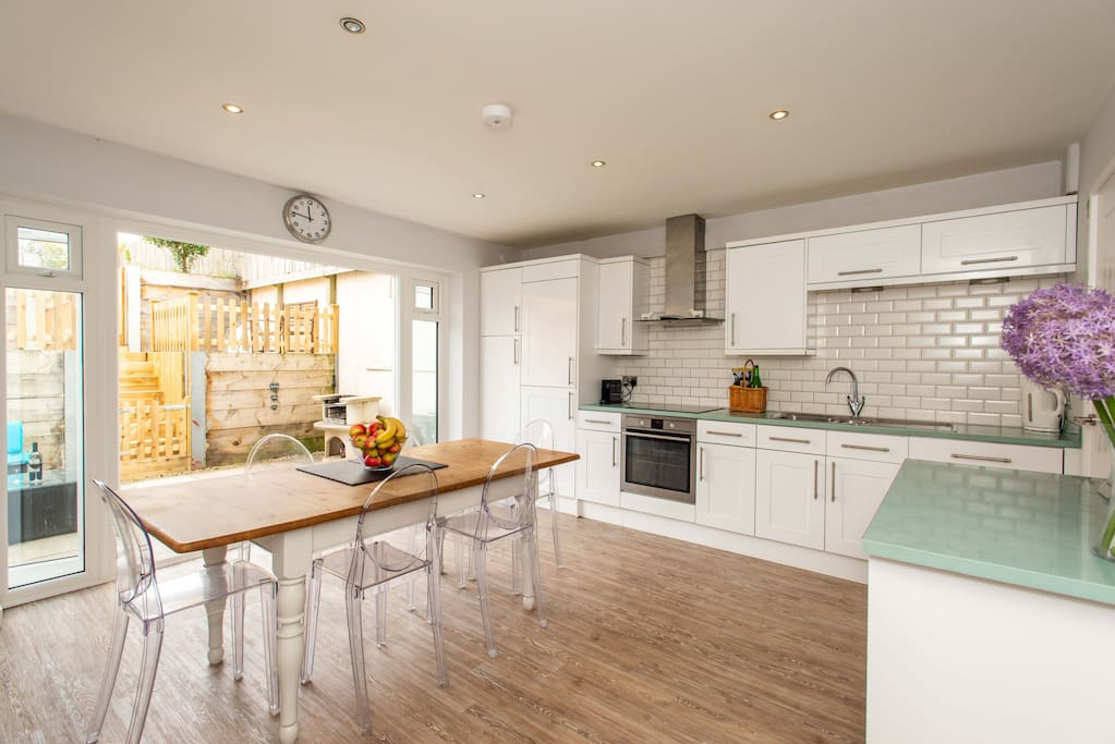 The fully equipped kitchen has double patio doors leading to BBQ and outside area