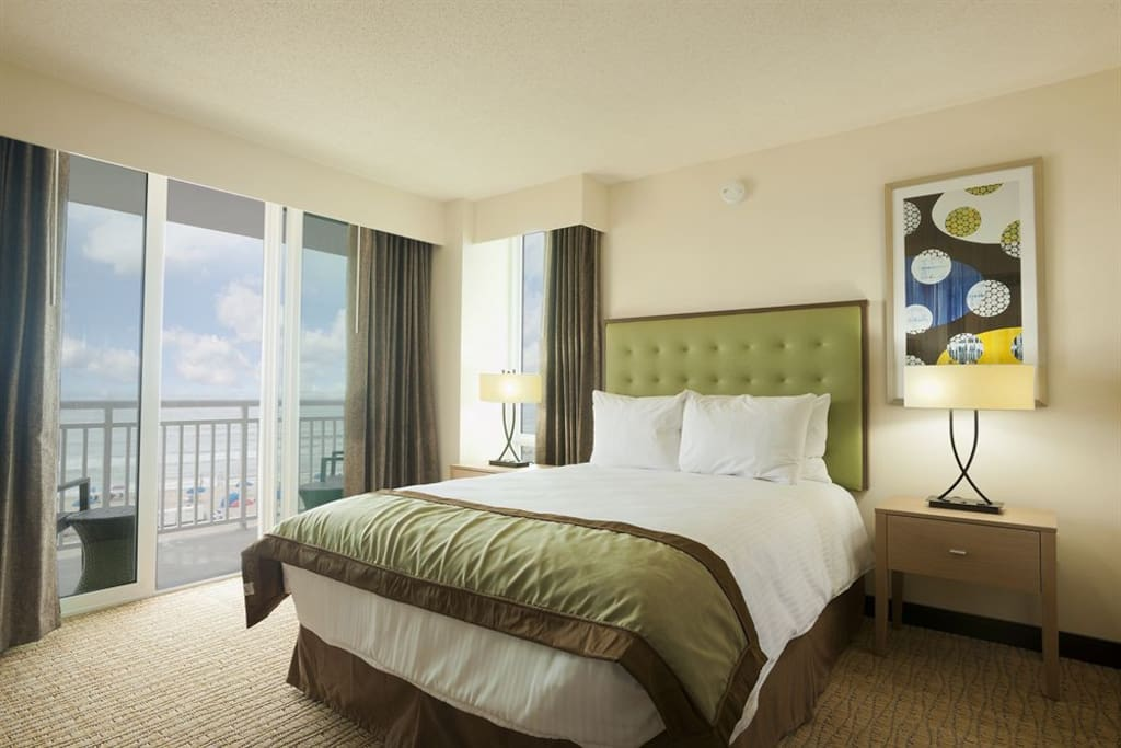 Bedroom with full bed, flat screen TV, and balcony with partial ocean views.