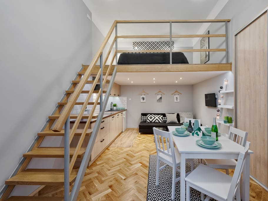 stairs to the mezzanine, bed, sofa, dining area