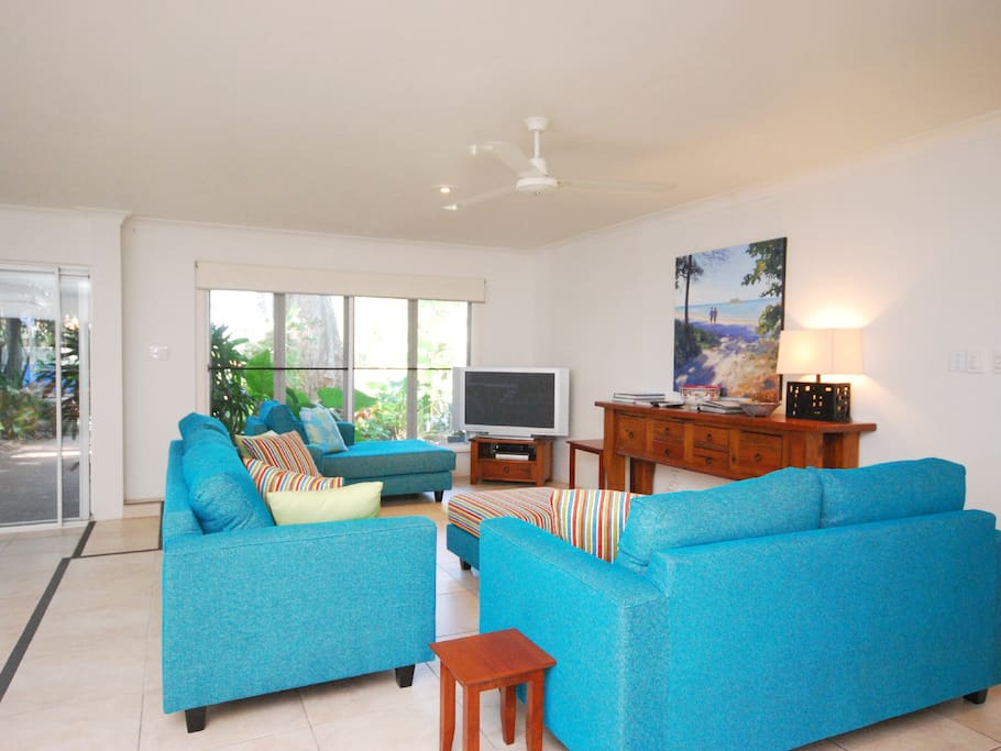 A spacious living area with comfortable lounge suite and a formal dining table, opens out to the wide covered patio