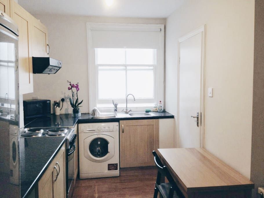 Kitchen includes ovens, microwave oven, a washing machine and a refrigerator.