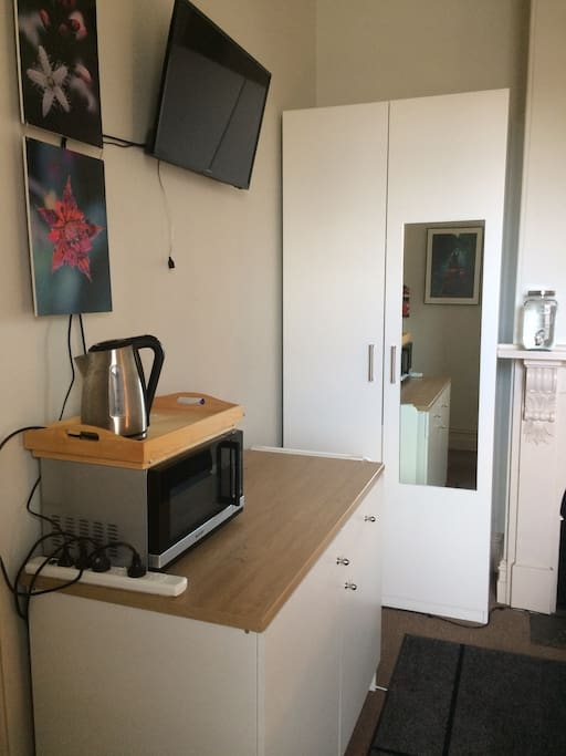 Your wall-mounted television, kitchenette (includes fridge, microwave, kettle, toaster, water dispenser, cutlery and crockery), full length mirror and large wardrobe