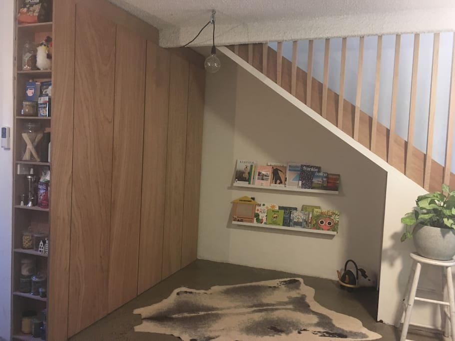 Kids play + reading nook with toys under the stairs