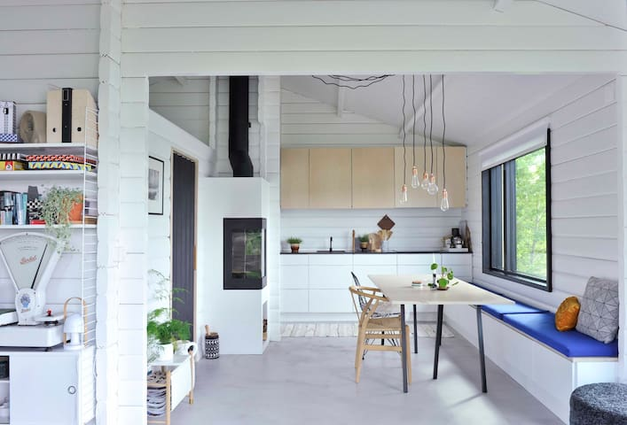 Kitchen and dining area with a view. Modern danish kitchen with the iconic Wishbone chair designed by Hans J. Wegner and Wire Chair from Vitra designed by Eames.