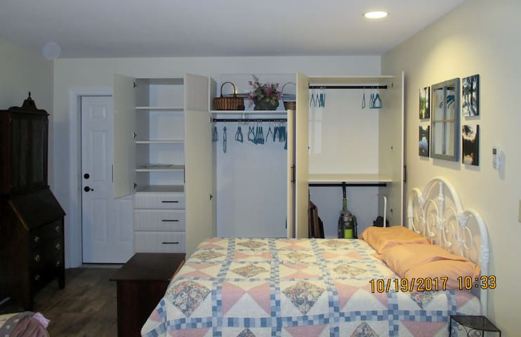 """Bed from living room area showing storage.  There is no reason to use the vaccum (shown here) or """"clean"""" before you go, just strip bed, putting sheets in laundry, wash dishes and take out the trash."""