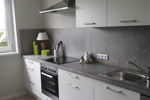 Die komplett eingerichtete Küche mit Herd und Spülmaschine